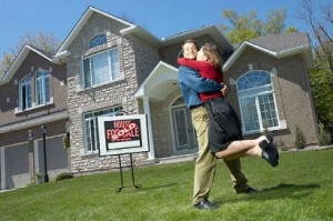 Embracing young couple who have just bought a house