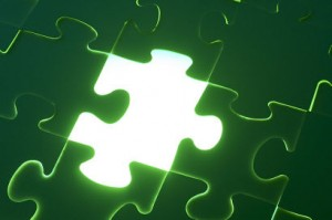 Green puzzle with missing piece shining with white light